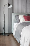 Black lamp  in modern bedroom design with red pillows. On bed Royalty Free Stock Images