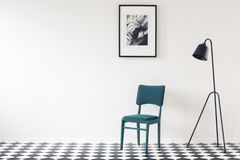 Minimal interior with copy space. Black lamp next to turquoise chair against white wall with poster and copy space in minimal interior Royalty Free Stock Photos