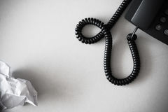 Black land line telephone and white crumpled paper on textured granite surface Stock Photos