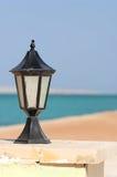 Black lantern along seashore Royalty Free Stock Photo