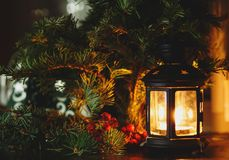 Black lantern with candle stands next to fir tree. Winter holidays, New year and Christmas celebration royalty free stock images