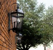 Black lanterns on brick wall in city street stock image