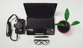 Black Laptop Black Camera and Plant Near Each Other on White Tile Royalty Free Stock Images