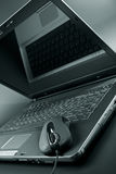 Black laptop and black mouse Royalty Free Stock Photo