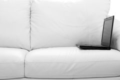 Black laptop computer on white sofa. A black laptop computer on white sofa Stock Photography