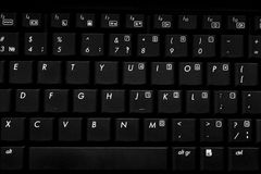 Black laptop keyboard. Black laptop keyboard with white letters and touchpad view from above with shallow depth of field Royalty Free Stock Image
