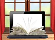 Black laptop and openned book on wooden table over window Stock Photography