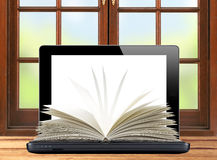 Black laptop and openned book wooden table over window Stock Photos