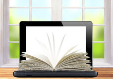 Black laptop and openned book on wooden table over window Royalty Free Stock Image
