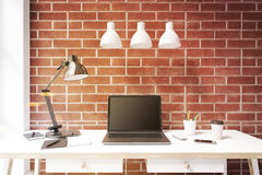 Black laptop screen, white desk, brick Stock Images