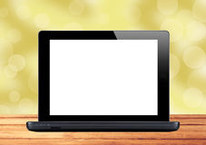 Black laptop on wooden table over blurred background Royalty Free Stock Photo