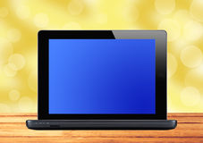Black laptop on wooden table over blurred background Royalty Free Stock Images
