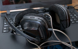 Black large dj headphones left on the laptop after mixing music Royalty Free Stock Image
