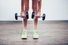 Black large dumbbell in the hands of the girls legs in green shoes, and bent down to the floor, close-up, white background stock photos
