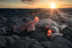 Red hot lava flows under beautiful sunset background stock photo