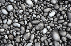 Black lava pebbles on beach Royalty Free Stock Images