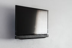 Black LCD or LED tv screen hanging on wall Stock Photo
