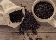 Black leaf tea. Cup of black leaf tea and small sack on a wooden table stock images
