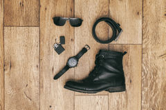 Black leather accessories on wooden floor grouped Stock Photo