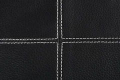 Black leather background stitched up by white. Thread Stock Images