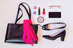 Black leather bag, black shoes, smartphone, glasses and cosmetic Stock Image