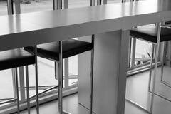 Black leather bar stool beside the window Stock Image