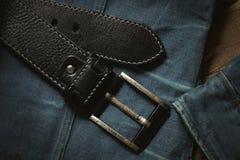 Black leather belt and blue denim jacket. Royalty Free Stock Photography