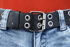 Black leather belt, blue jeans. Black leather belt with metal buckle and blue jeans royalty free stock photography