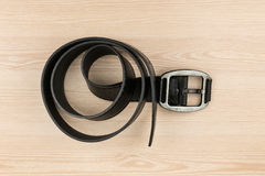 Black leather belt with buckle lying on a wooden surface Royalty Free Stock Image