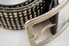 Black leather belt closeup. A black leather belt with nails on a white background Stock Photos