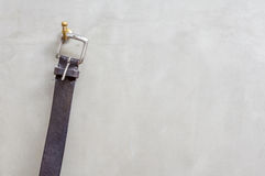 The black leather belt hanging on the hanger with exposed concre Stock Photo