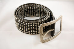 Black leather belt roundup. A black leather belt with nails on a white background Royalty Free Stock Photo