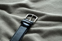 Black leather belt on wrinkles. A black leather belt with silvery metal rests on wrinkled textile Stock Image