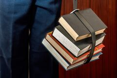 Black Leather Book Strapped Around Four Books Stock Image