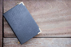 Black leather book on wood background. Education concept Royalty Free Stock Photos