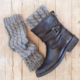 Black leather boot and grey knitted wood legwarmers stock image