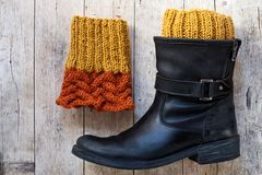 Black leather boot and knitted wood legwarmers royalty free stock image