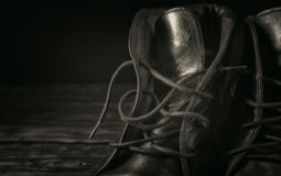 Black leather boots closeup. On a black background closeup with copy space. Black and white toning stock photo