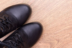 Black leather boots over wooden background Stock Photos