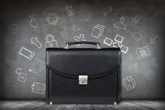 Black leather briefcase over gray wall Royalty Free Stock Photos