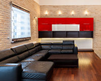 Black leather couch in apartment Royalty Free Stock Image