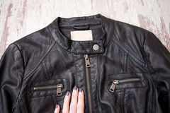 Black leather jacket with a zipper and a female hand. Fashion concept, close up Royalty Free Stock Photos