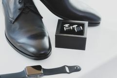 Black leather male dress shoes, cufflinks and watch. On white background Stock Images