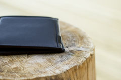 Black, leather man's wallet sitting on wood. / log. The image has a rustic feel combined with a fashionable, classy, modern, atmosphere. The image was taken stock images