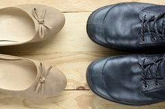 Black leather man shoes opposite an elegant beige woman shoes Royalty Free Stock Photos