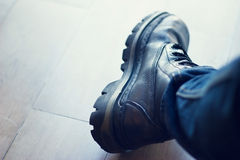 Black leather men's boot on wooden floor background. Black leather men's boot on old wooden floor background Royalty Free Stock Image