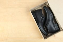 Black leather men`s shoes. In a box for shoes on a wooden background Royalty Free Stock Photo