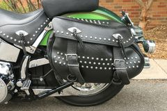 A black leather motorcycle saddlebag with studs, fringes and buckles. A black leather motorcycle saddlebag pannier with studs, fringes and buckles Royalty Free Stock Images