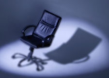 Black leather office chair in spotlight royalty free stock photos