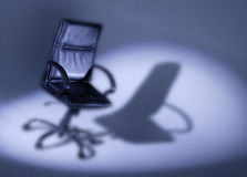 Black leather office chair in spotlight royalty free stock photo